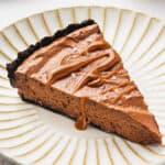 slice of chocolate mousse pie drizzled with caramel on ornate plate
