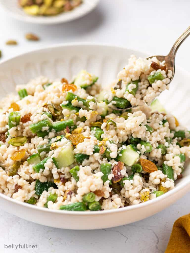 couscous salad in white bowl with spoonful