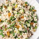 overhead Israeli Couscous Salad with golden raisins and green beans on white plate