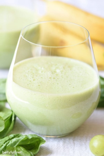 glass filled halfway with green smoothie