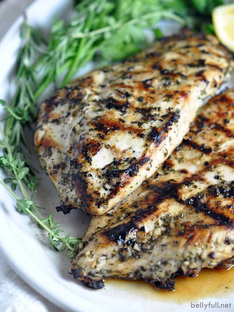 whole grilled chicken breasts on serving plate