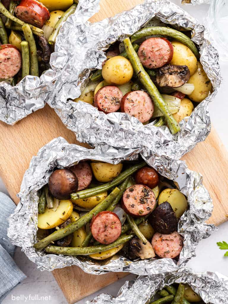 overhead cooked sausage and veggie foil packets on cutting board