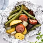 close up cooked kielbasa and vegetable foil packet dinner