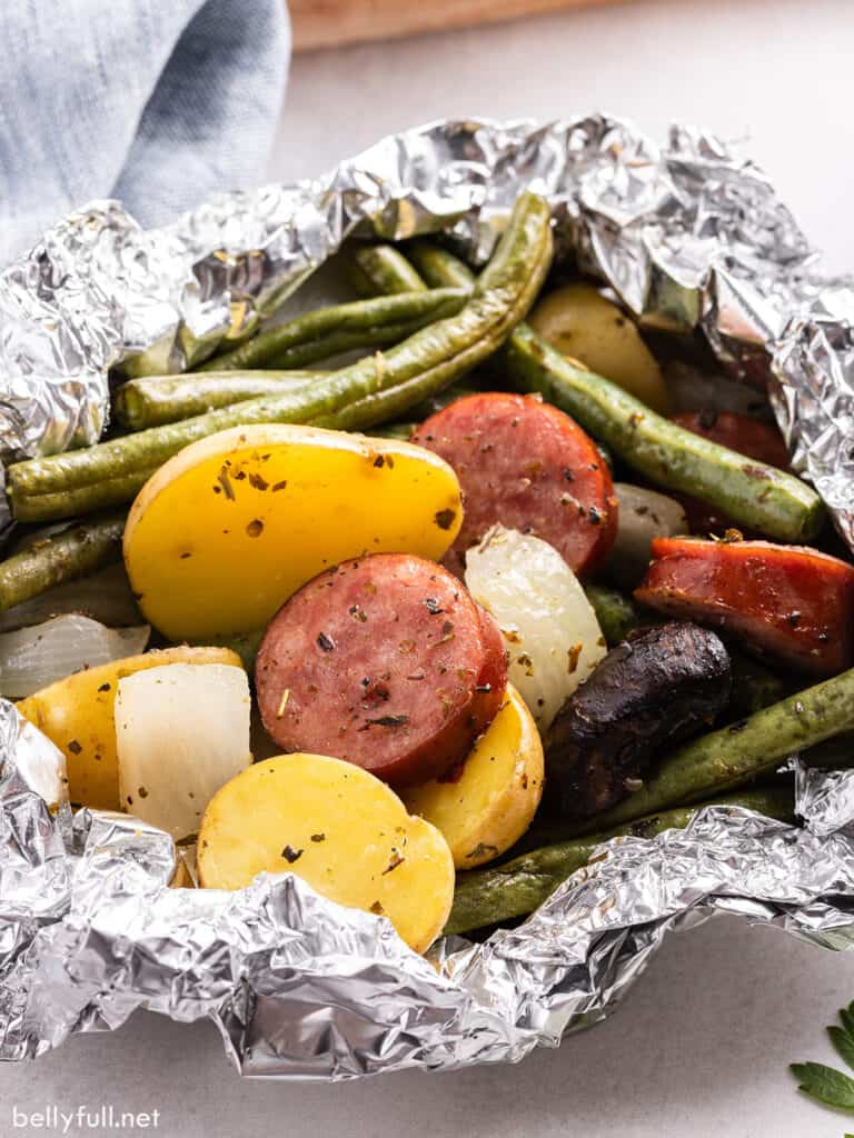 close up cooked sausage and vegetable foil packet dinner