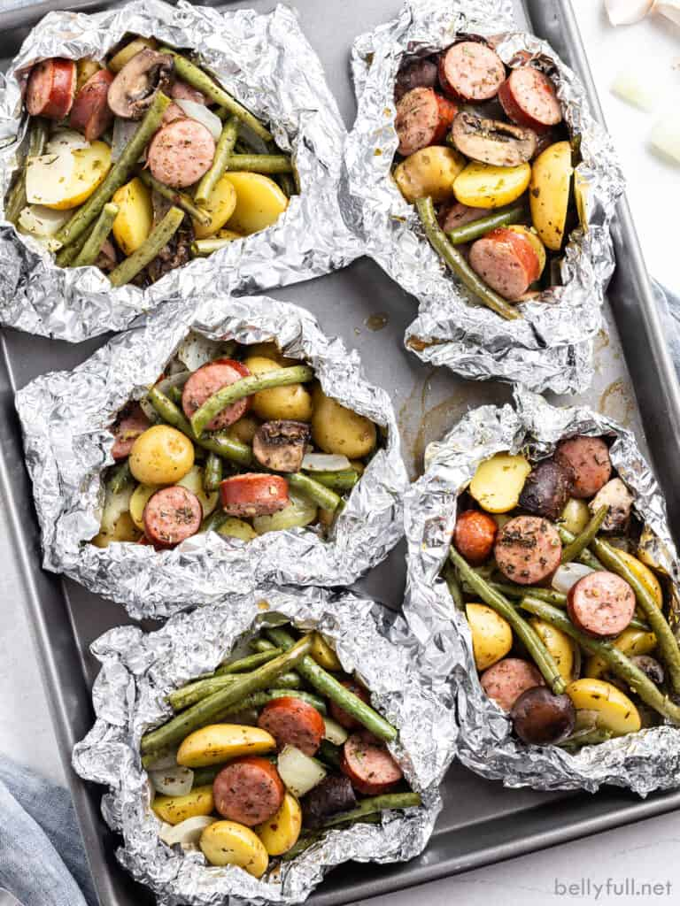 overhead 5 cooked sausage foil packets on baking sheet