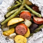 close up cooked kielbasa and vegetable foil packet meal