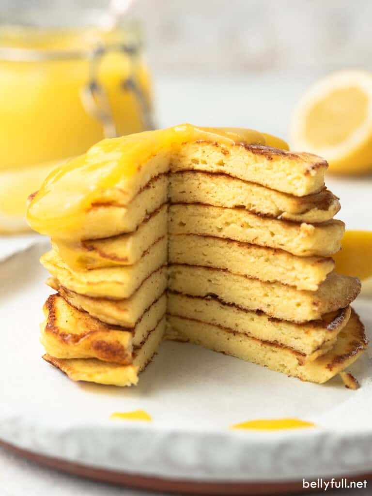 stack of 7 pancakes sliced into with lemon curd topping