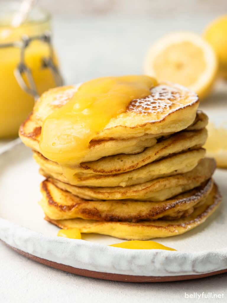 tall stack of lemon ricotta pancakes with lemon curd on top