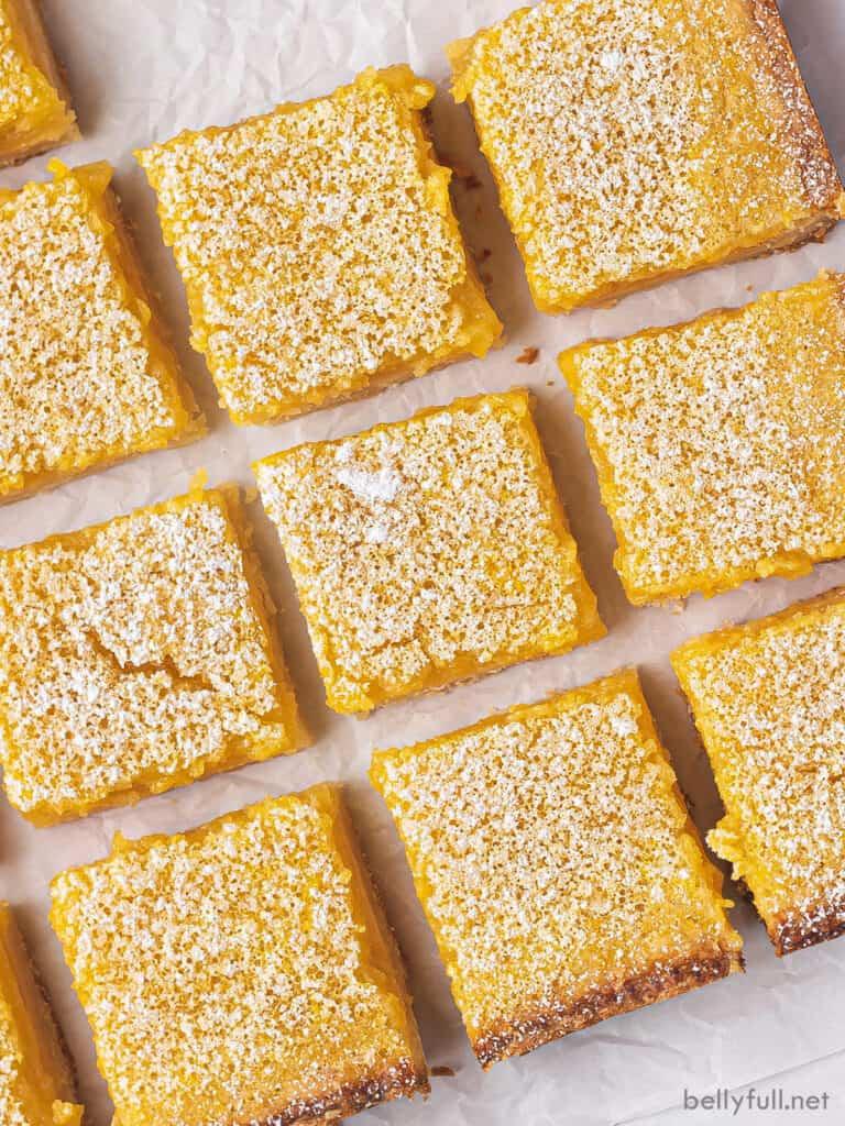 overhead close up cut lemon bar squares on parchment paper