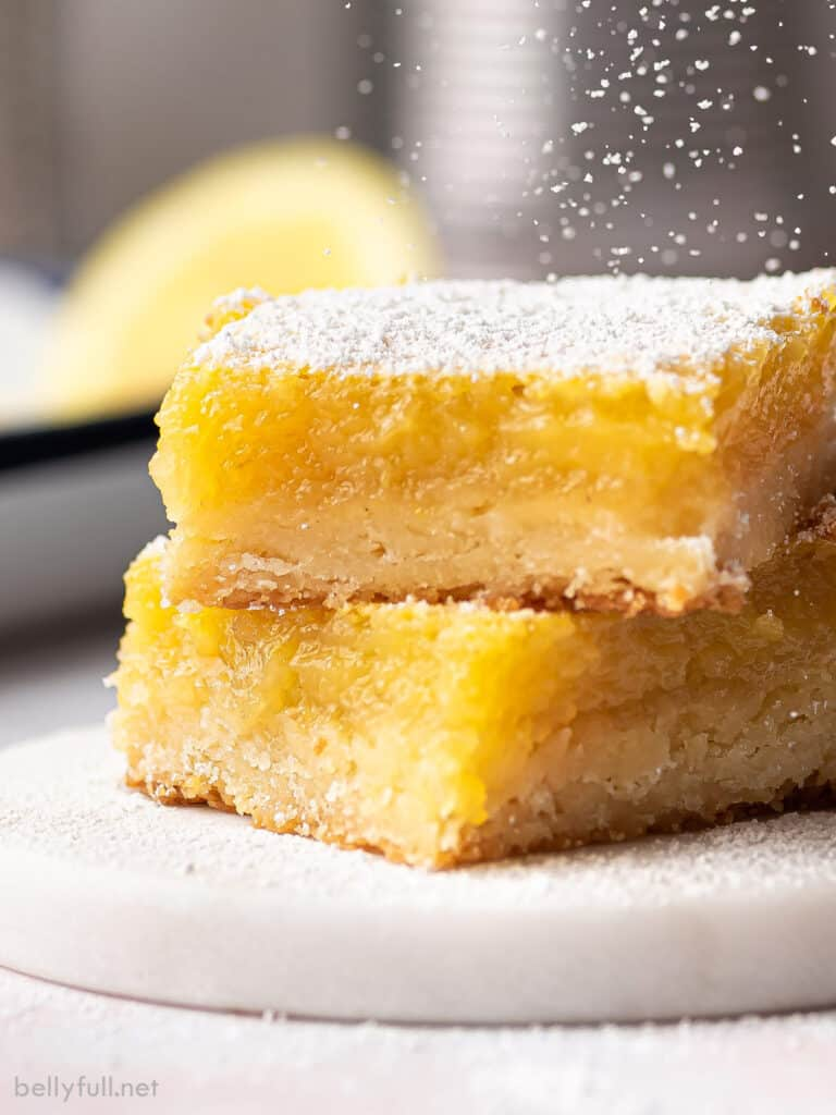 two lemon bars stacked with powdered sugar
