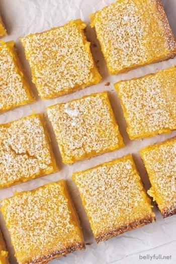 overhead close up cut lemon bars on parchment paper