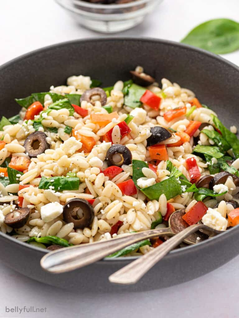 pasta salad with spinach, red bell pepper, and feta cheese in bowl