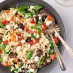 overhead bowl of Mediterranean Orzo Salad with serving spoons
