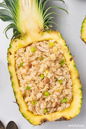 coconut rice piled inside fresh hollowed out pineapple half with spoon