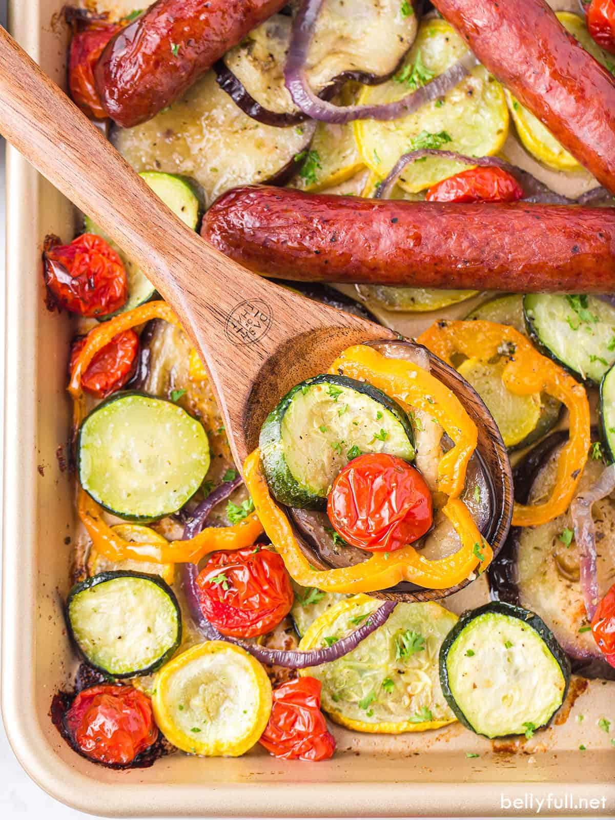 A wooden spoon with zucchini, orange pepper and a cherry tomato, over sheet pan ratatouille
