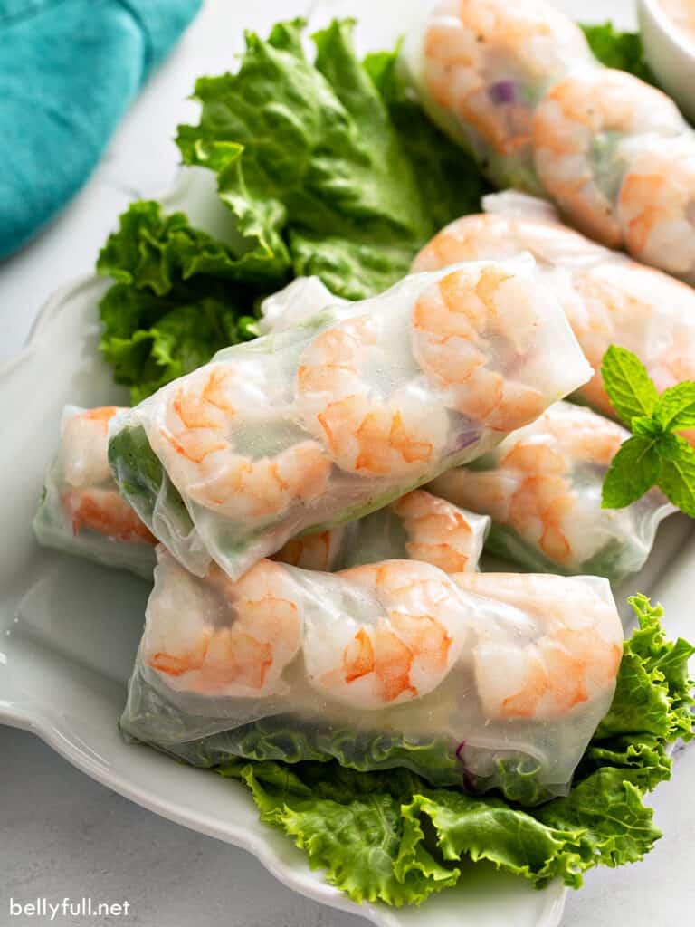 close up fresh shrimp spring rolls on lettuce lined white plate