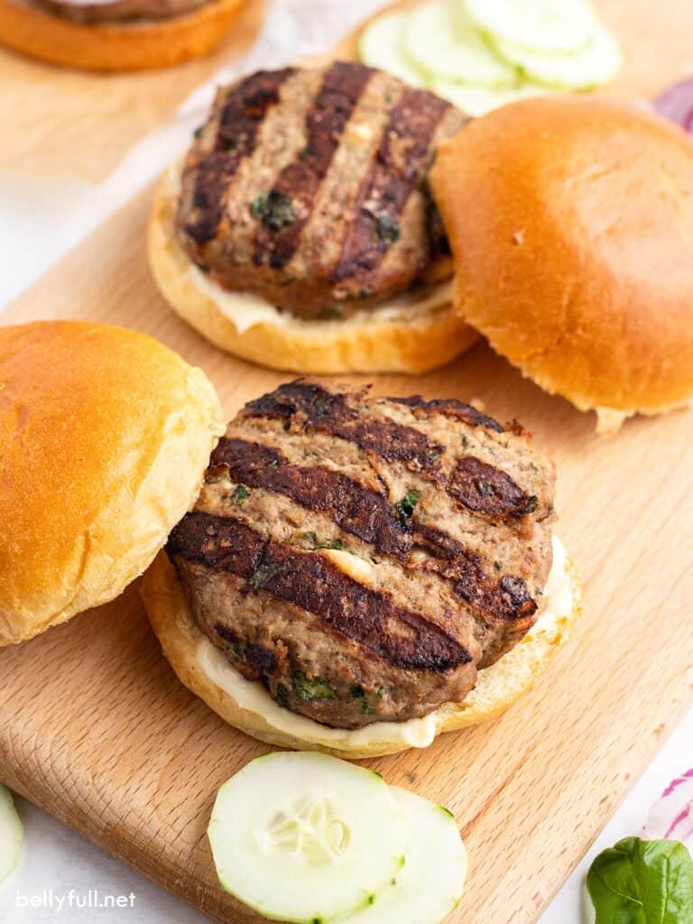 grilled burger on bun sitting on cutting board