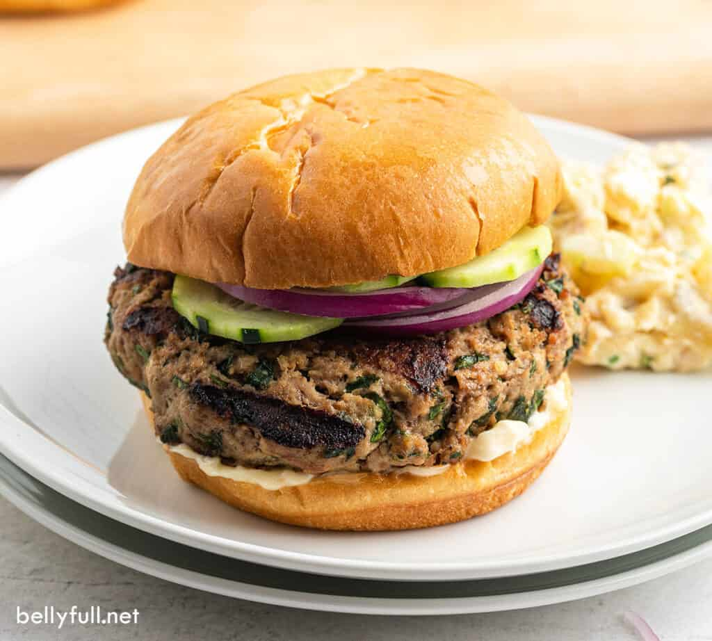 grilled turkey burger with cucumber and onion slices on white plate