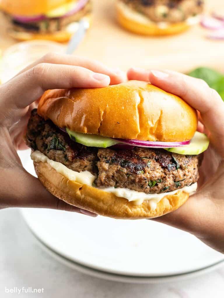 hands holding grilled turkey burger on bun