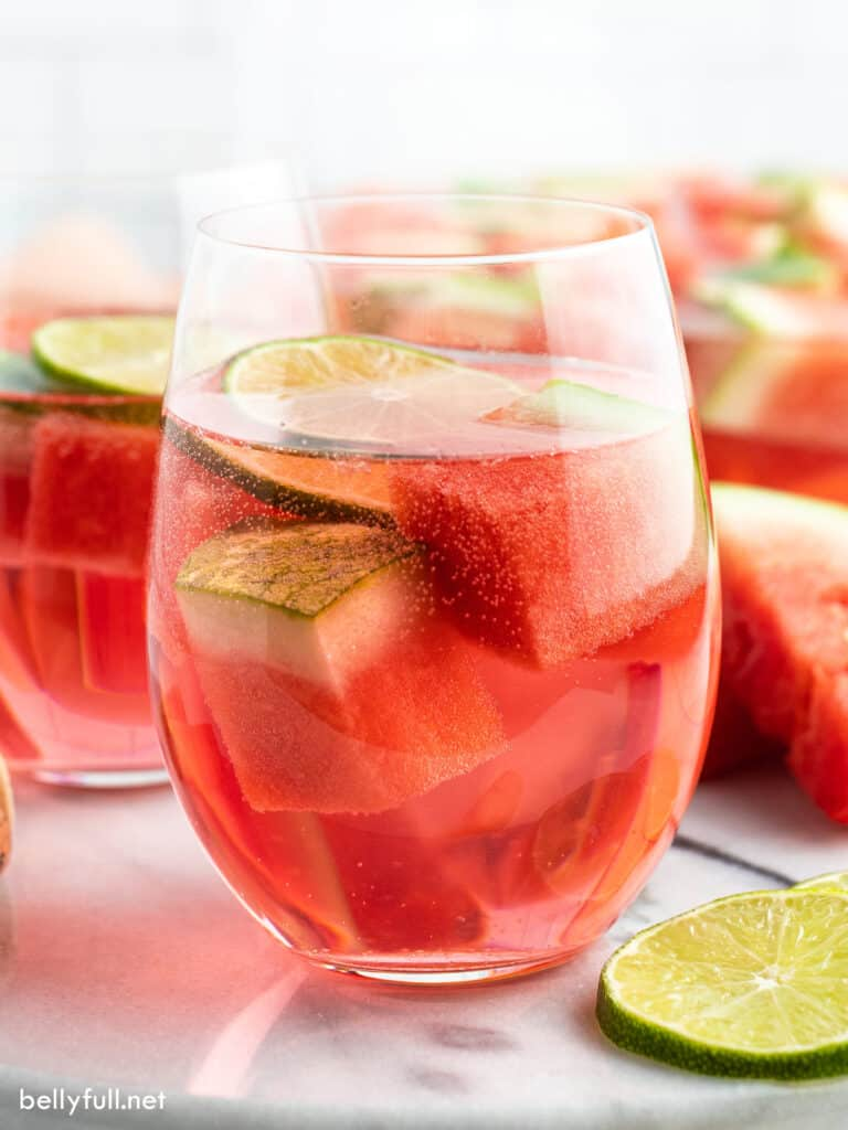 glass with watermelon cubes, wine, and lime slice