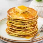 stack of zucchini ricotta pancakes with slab of butter on top