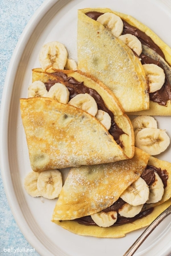 close up overhead 3 banana nutella crepes on white plate