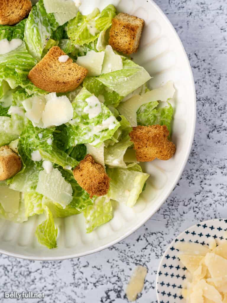 overhead close up salad with Romaine lettuce, shaved parmesan, and croutons