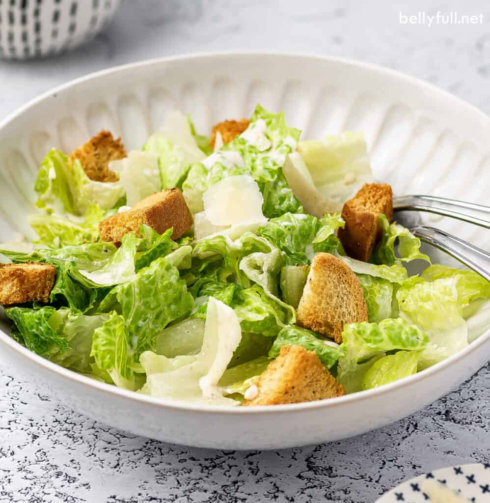 romaine salad with croutons and shaved Parmesan in white bowl