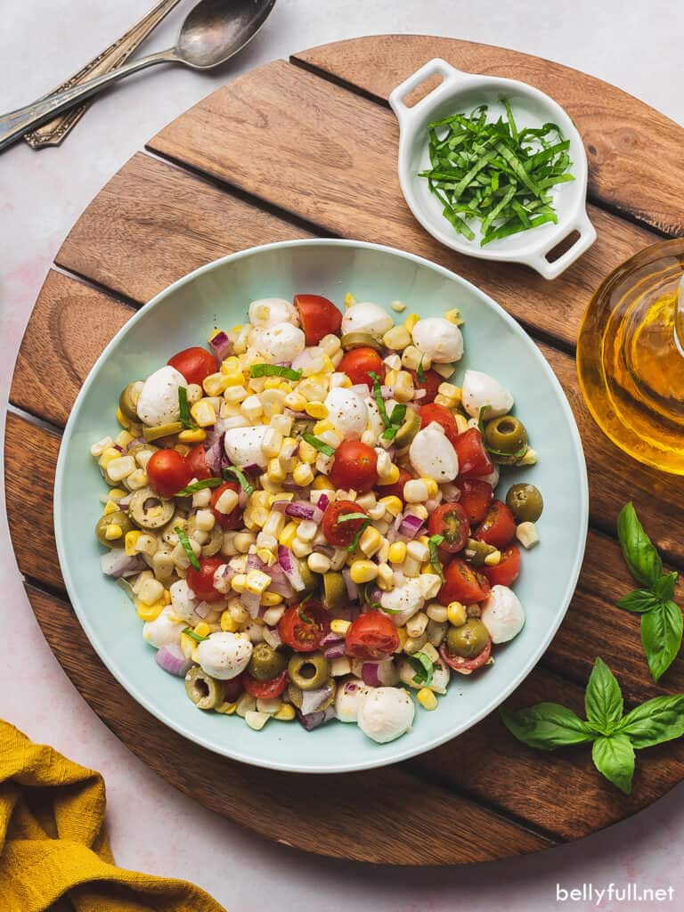 overhead corn salad with tomatoes and mozzarella in serving bowl