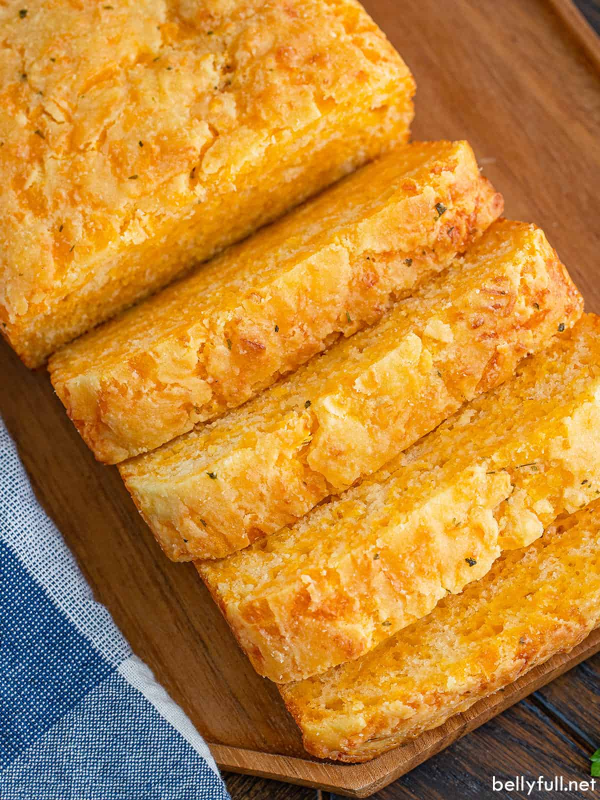 A loaf of cheese bread with four pieces sliced