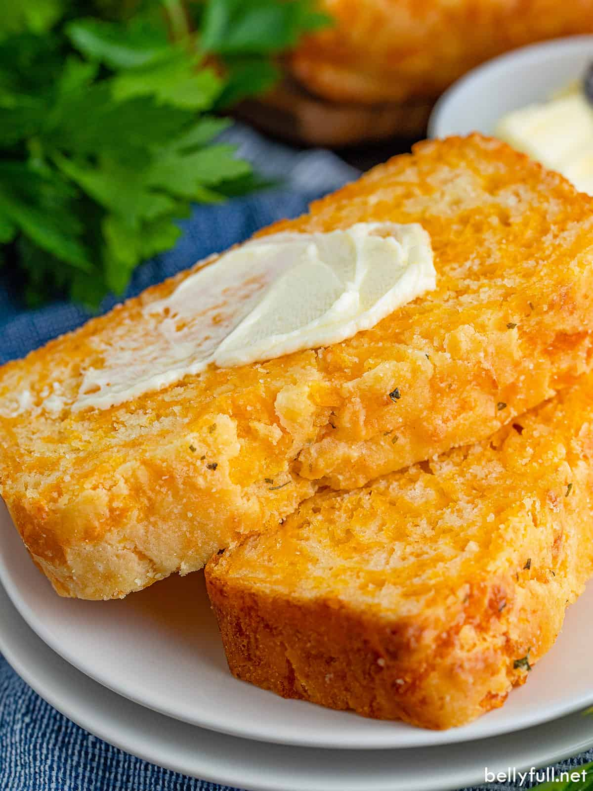Two slices of cheesy quick bread, the top slathered with butter