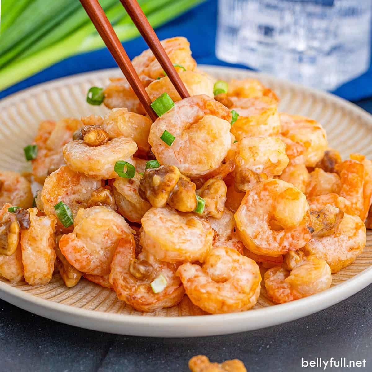 Chopsticks picking up a piece of shrimp from a plate of honey walnut shrimp