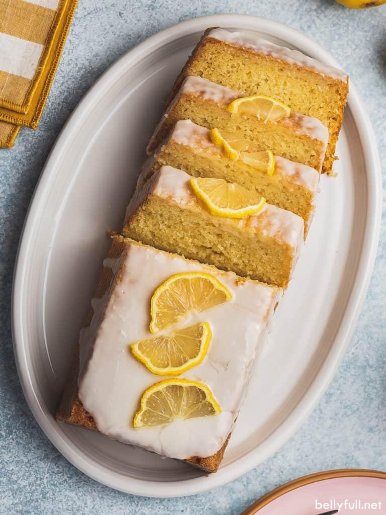 overhead iced lemon loaf pound cake garnished with lemon slices