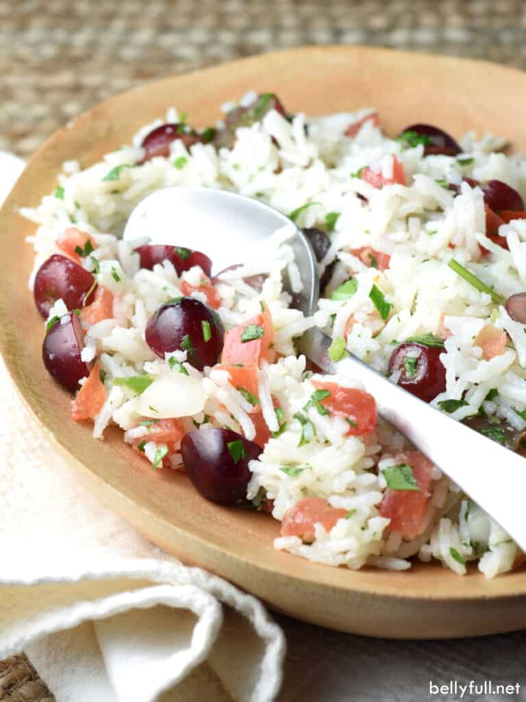 rice and grape salad in dish with serving spoon