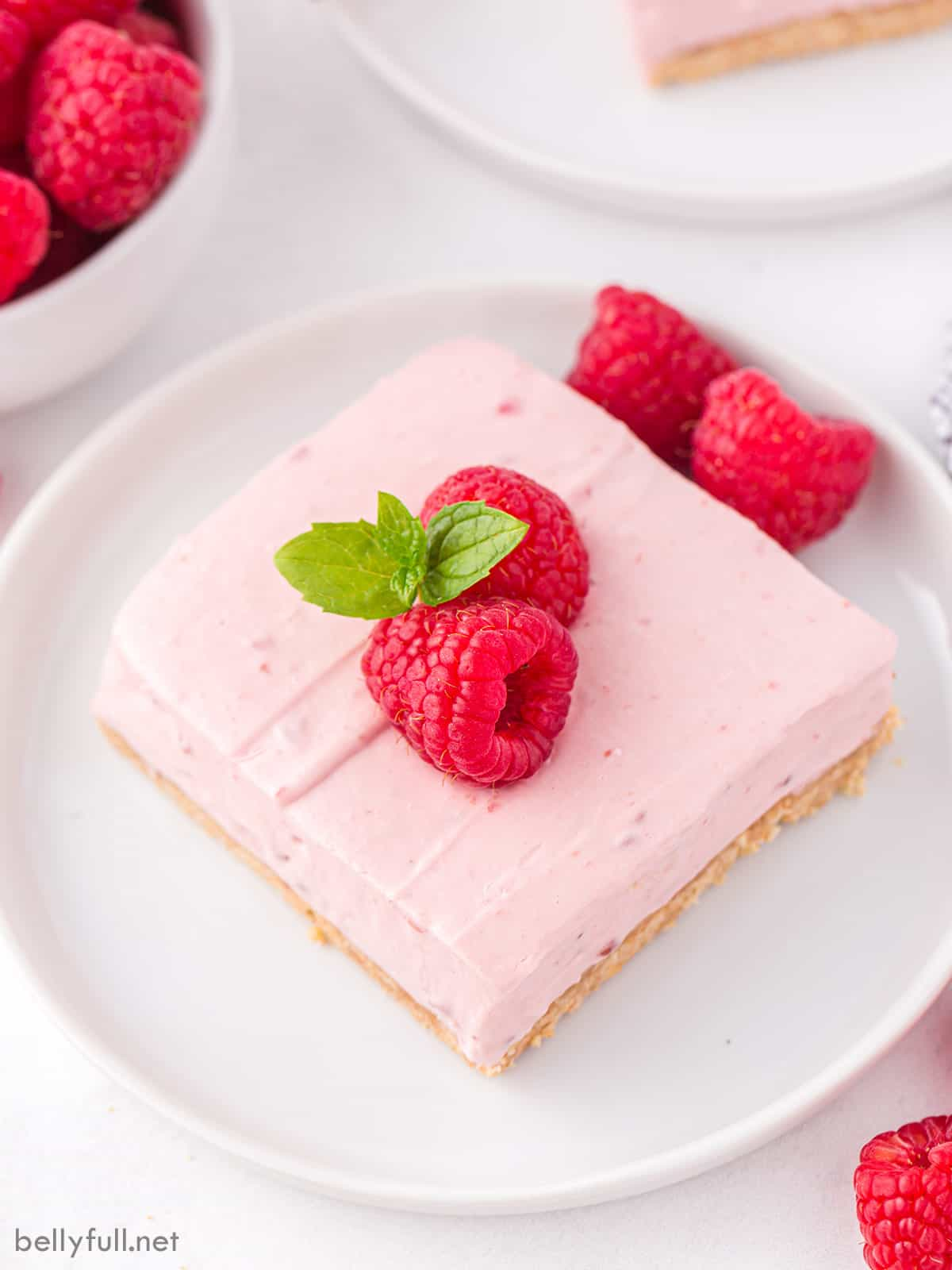 A raspberry bar topped with fresh raspberries on a white plate