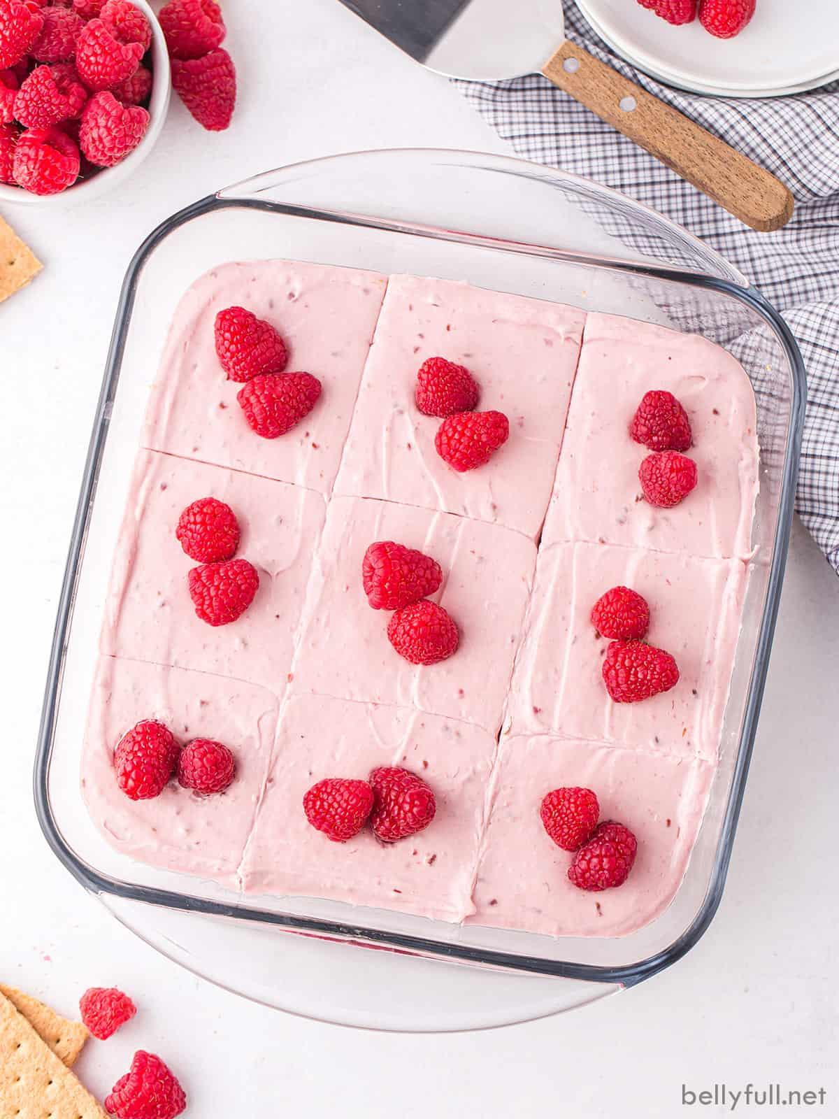 No-bake raspberry cheesecake bars topped with fresh raspberries in a baking dish