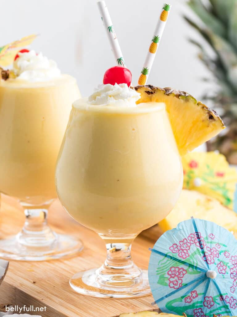 pina colada in glass with whipped cream, pineapple wedge, and maraschino cherry