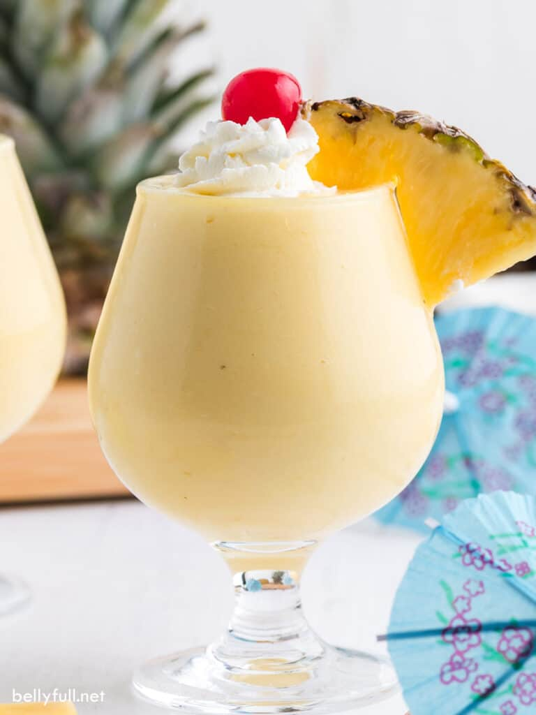 tropical fruity blender drink with pineapple wedge and pina colada in glass with whipped cream, pineapple wedge and maraschino cherry