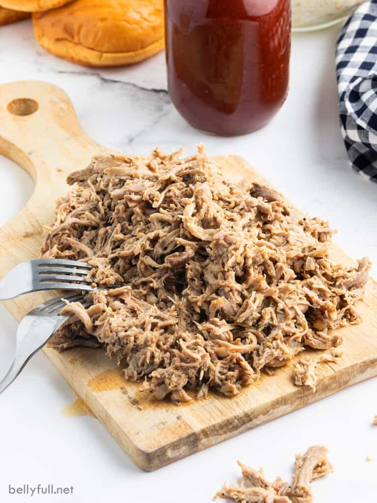 pulled pork on cutting board with 2 forks
