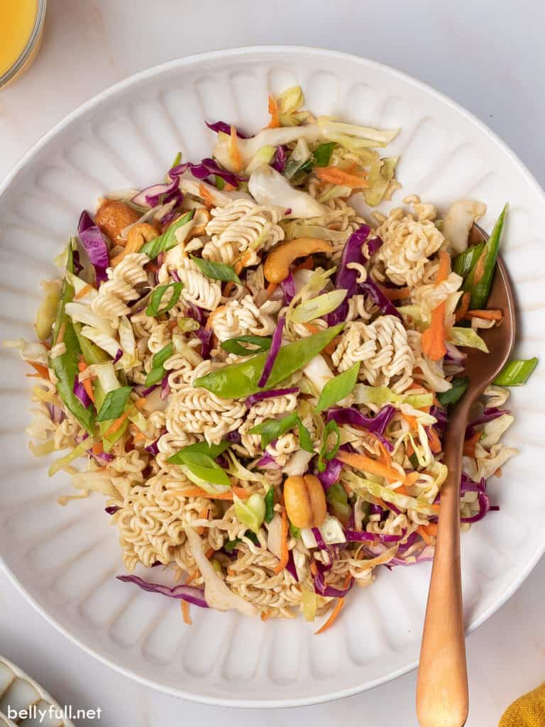overhead ramen noodle salad in bowl with serving spoon
