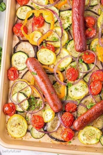 A baking sheet of sheet pan ratatouille with smoked sausage links