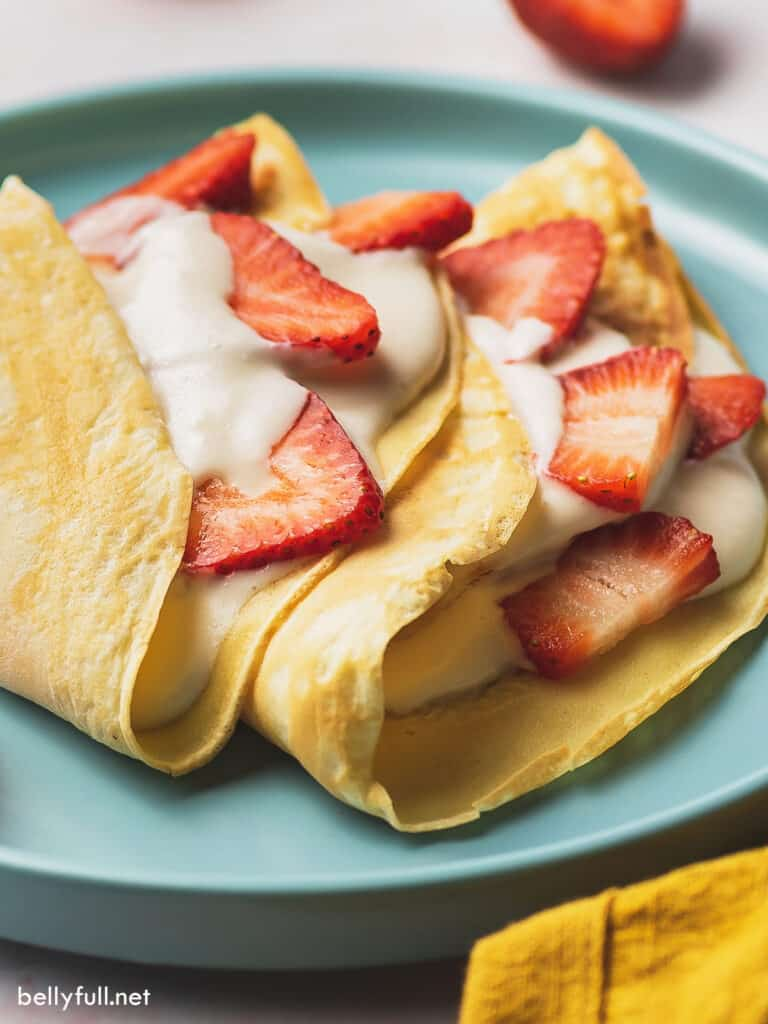 close up strawberry crepes with cream filling and fresh sliced strawberries