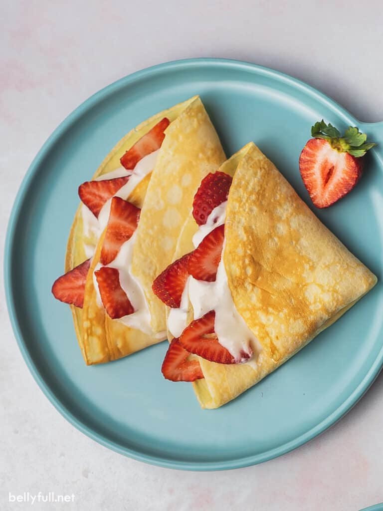 overhead crepes on plate with cream filling and sliced strawberries