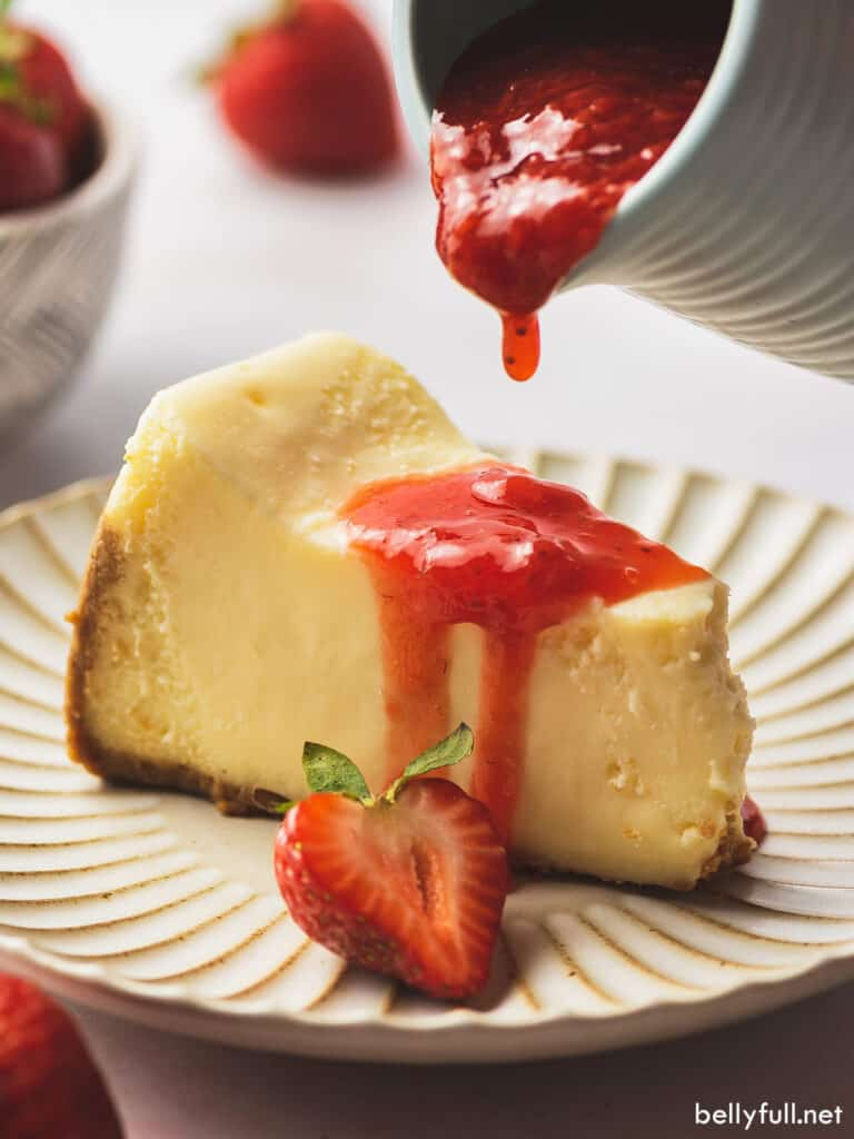 strawberry topping drizzled over slice of cheesecake