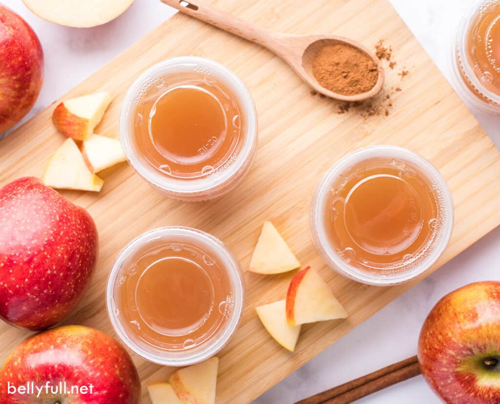 Apple pie shots on a wood countertop, with small apple wedges in the center