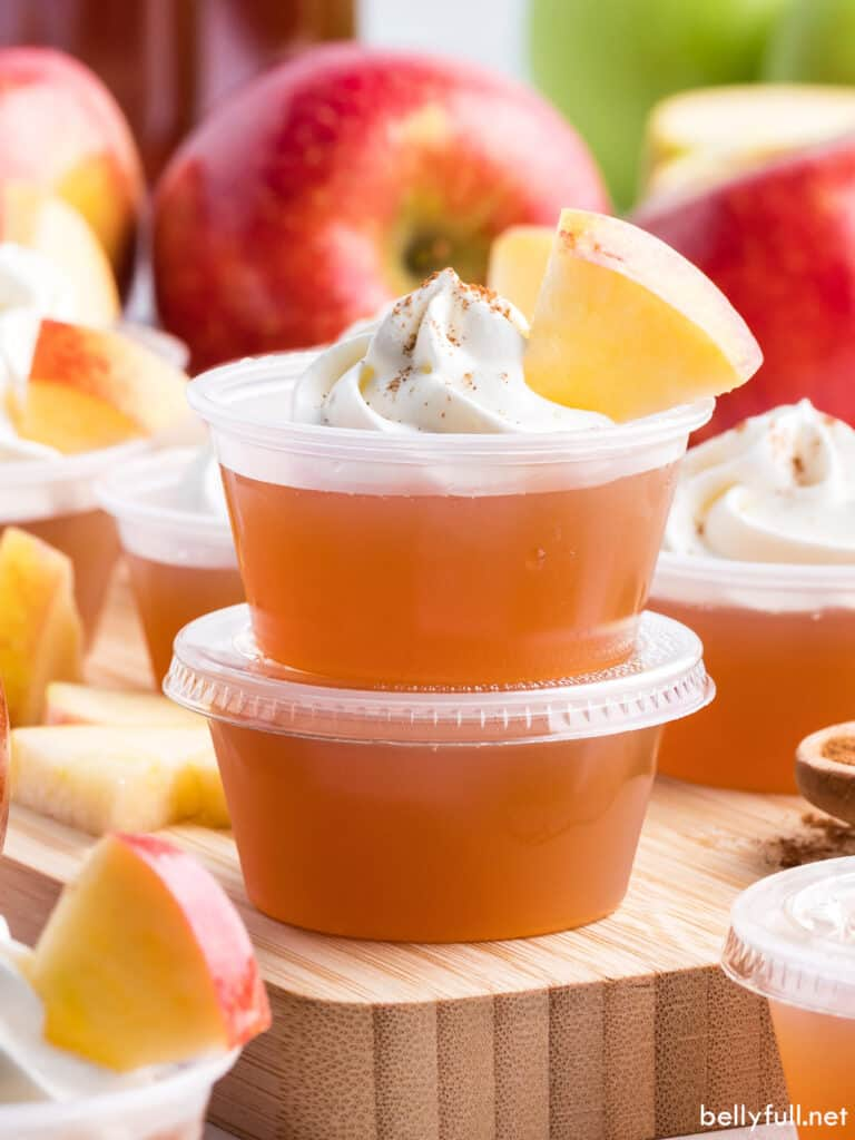 Two stacked apple jello shots with whipped cream and cinnamon