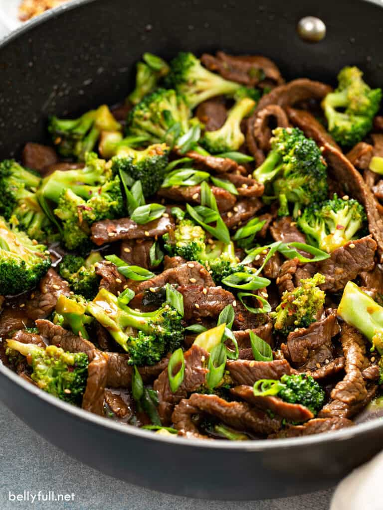 close up beef and broccoli stir fry with scallions in pan