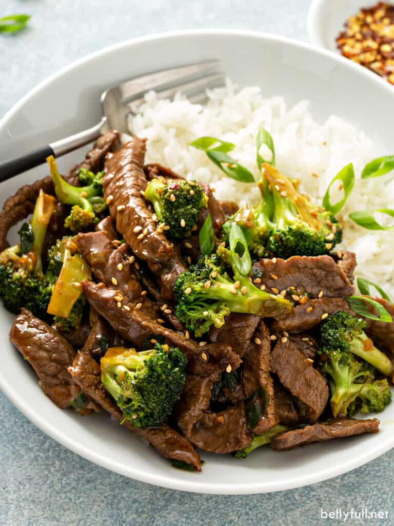 beef stir fry with broccoli over white rice in bowl