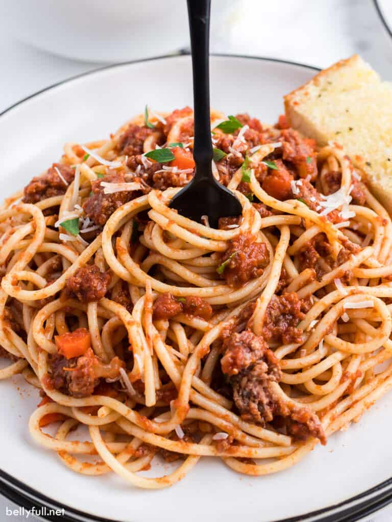 cooked spaghetti with meat sauce being swirled with fork