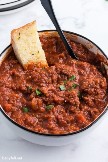 Bolognese sauce in bowl with slice of garlic bread